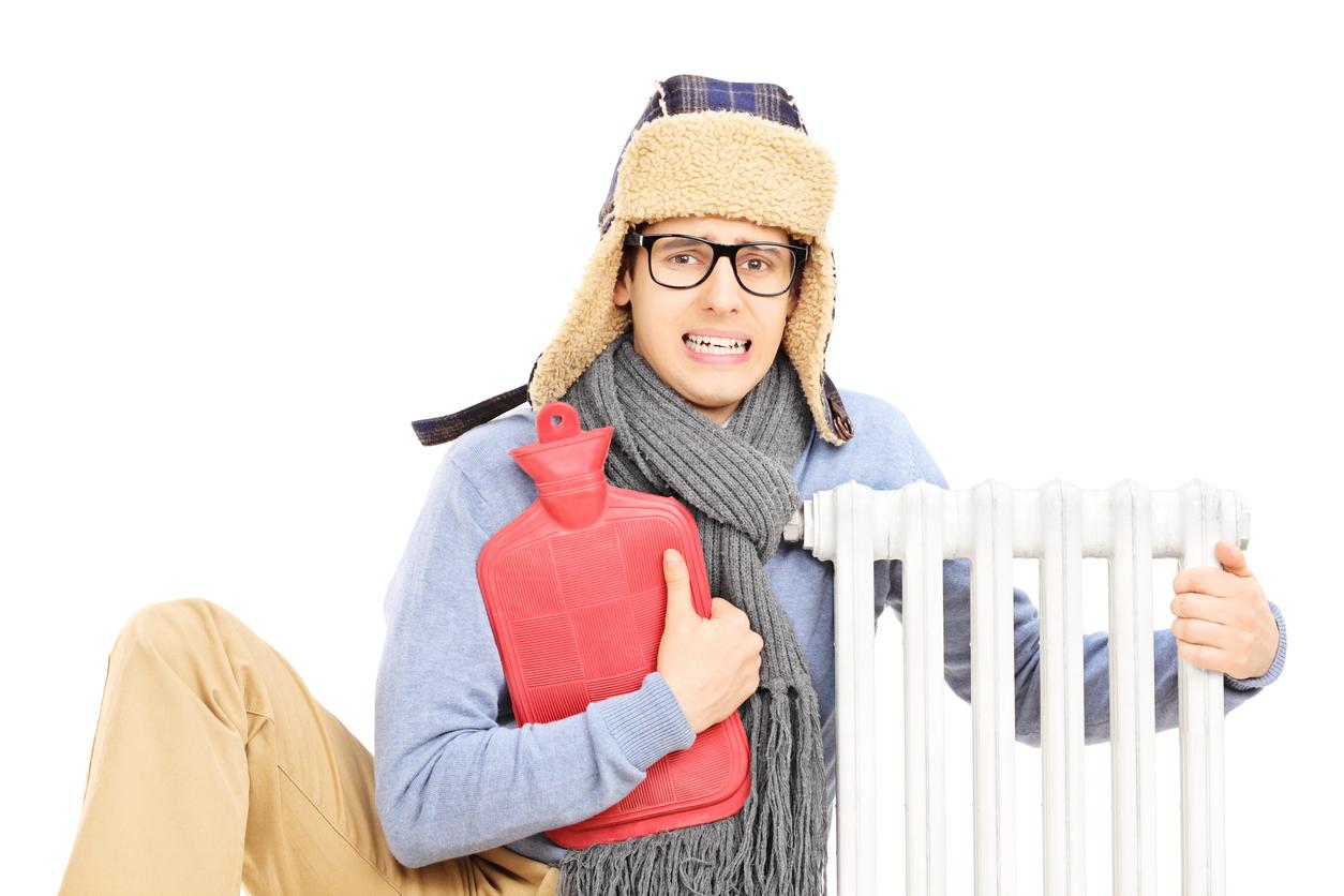 Jongeman met muts en sjaal aan, zit aan de verwarming met een warmwaterkruik.